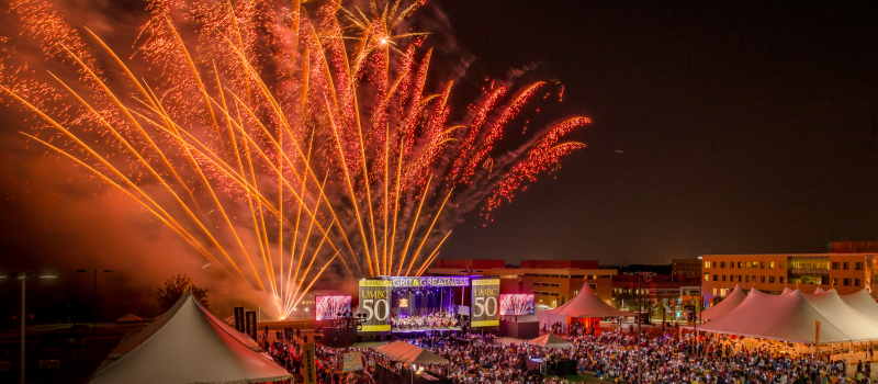 UMBC campus at nighttime while celebrating the university's 50th anniversary with a huge crowd and sky of fireworks.