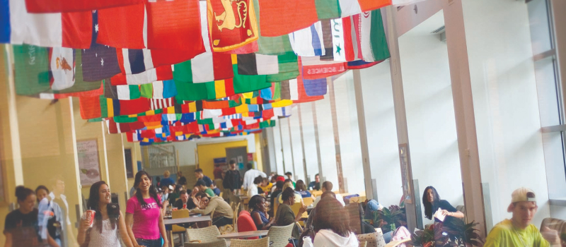 A large room of college students eat together beneath a ceiling full of international flags.