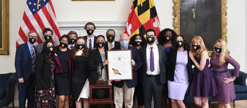 A group of student men and women in business casual clothing pose with Maryland Governor Larry Hogan to celebrate their Mock Trial win. They are holding up a large certificate at the center of the group.