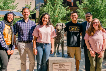 A group of students gathers around a statue of a dog, UMBC's mascot.