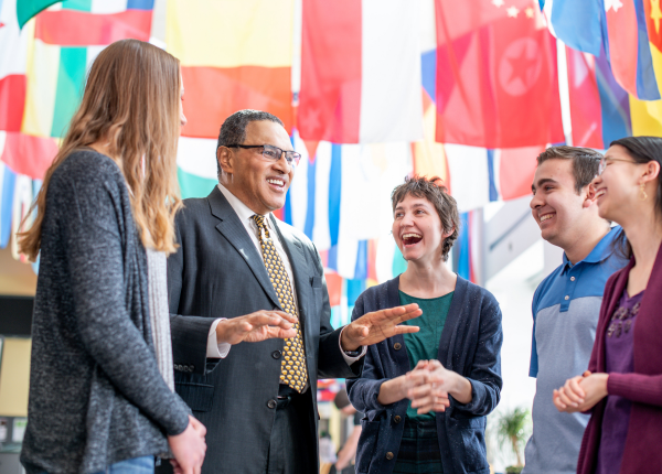 President Hrabowski talks with a group of college students in a room with international flags across the ceiling.