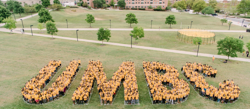 Hundreds of students in gold-colored t-shirts gather on a field to create the shape 'UMBC' with their bodies.